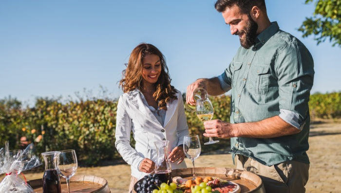 Couple eating and drinking wine in vineyard